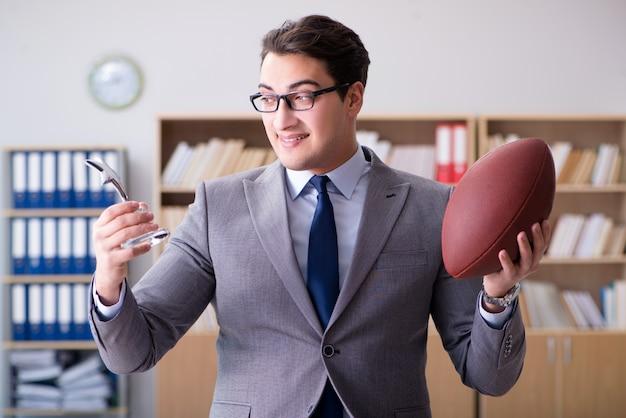 Geschäftsmann mit amerikanischem fußball im büro