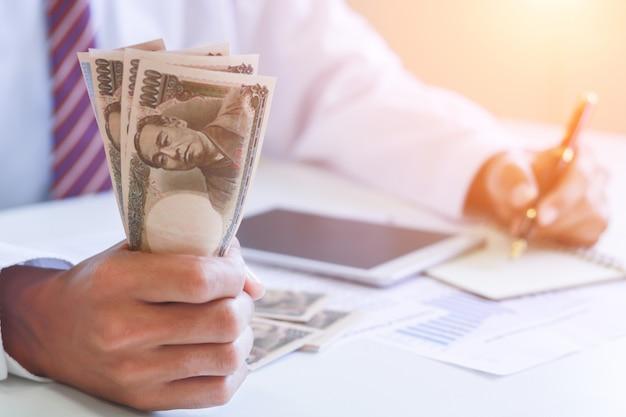Geschäftsmann mit bargeld-yen