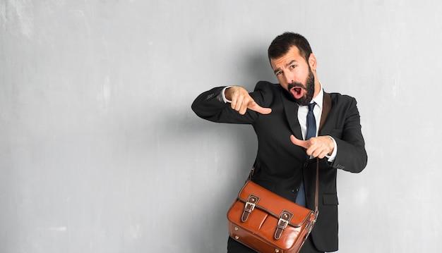 Geschäftsmann mit bart mit dem finger auf jemanden zeigen und viel lachen