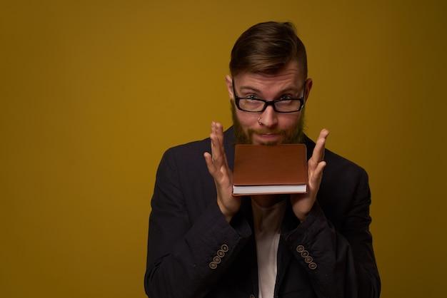 Geschäftsmann mit brillennotizblock in den händen eines studiobeamten. foto in hoher qualität