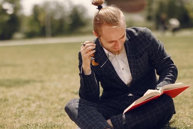 Geschäftsmann mit buch, das in einer sommerstadt sitzt