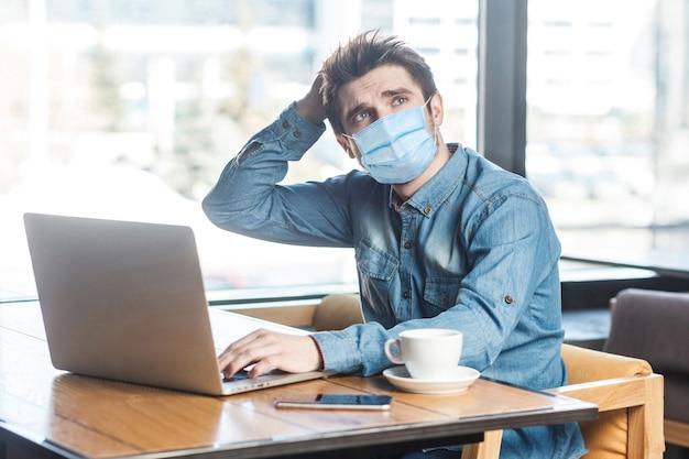 Geschäftsmann mit chirurgischer medizinischer maske im blauen hemd, der auf laptop sitzt und tippt, neue idee hat und eigene strategie plant, eine hand auf dem kopf hält. indoor-arbeits- und gesundheitskonzept.