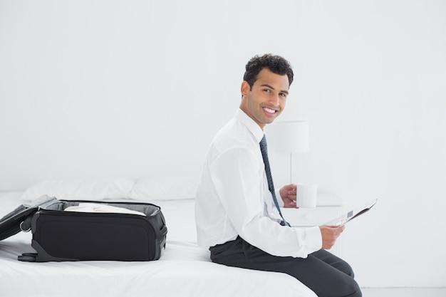 Geschäftsmann mit cup und zeitung durch gepäck in einem hotelzimmer Premium Fotos