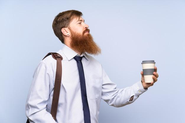 Geschäftsmann mit dem langen bart, der kaffee hält, um wegzunehmen