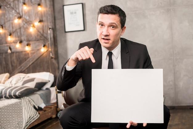 Geschäftsmann mit dem leeren papier, das auf stuhl sitzt