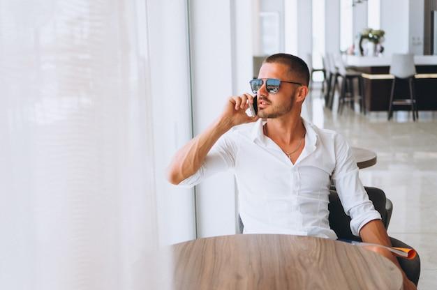Geschäftsmann mit dem telefon, das am tisch sitzt