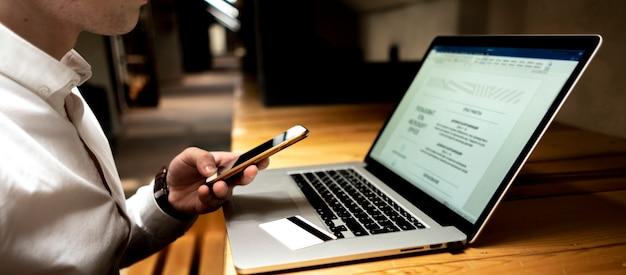 Geschäftsmann mit dem telefon, laptop und karte, die elektronische zahlung auf seinem arbeitsplatz tun