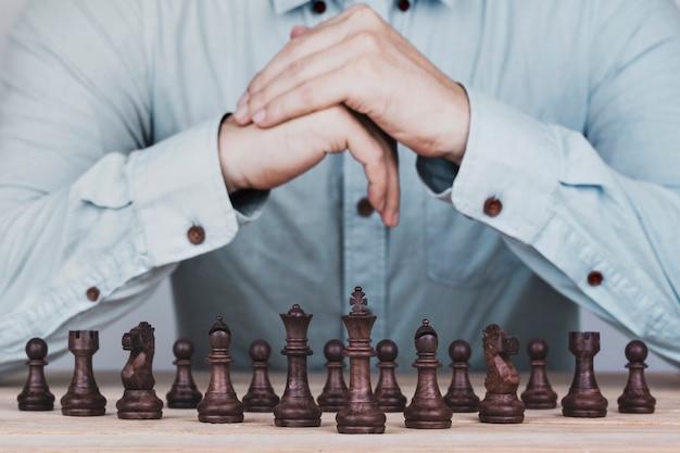 Geschäftsmann mit den gefalteten händen eine brainstormingplanungsstrategie im wettbewerbserfolgsspiel, in der konzeptstrategie und im erfolgreichen management oder in der führung