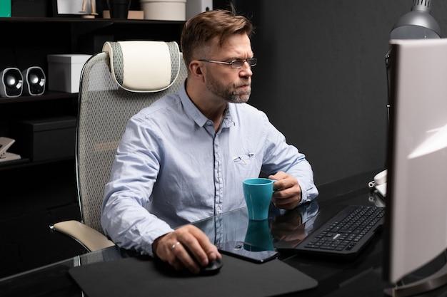 Geschäftsmann mit den gläsern, die im büro am computertisch arbeiten und kaffee von der hellen schale trinken