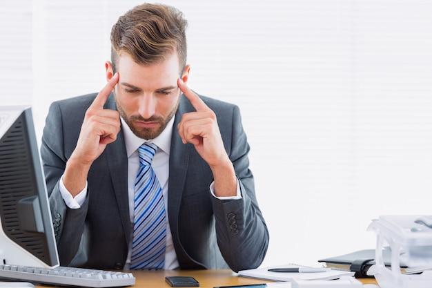 Geschäftsmann mit den schweren kopfschmerzen, die am schreibtisch sitzen