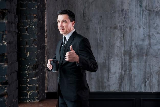 Geschäftsmann mit der kaffeetasse, die sich daumen zeigt und kamera betrachtet