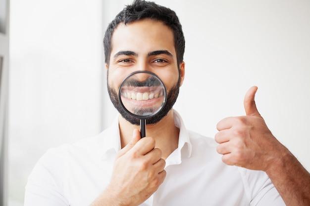 Geschäftsmann mit der lupe, die auf sein lächeln laut summt