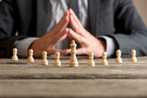 Geschäftsmann mit der planungsstrategie der gefalteten hände mit der schachfigurenkönigin und den bauern auf einem alten holztisch.
