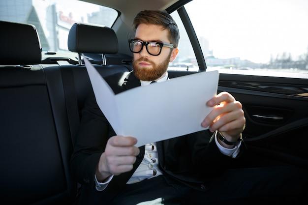 Geschäftsmann mit dokumenten, die auf auto-rücksitz fahren
