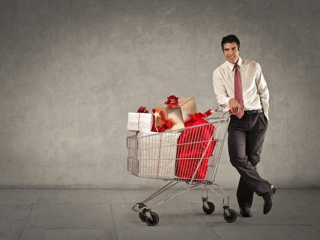 Geschäftsmann mit einem einkaufswagen voller geschenkboxen