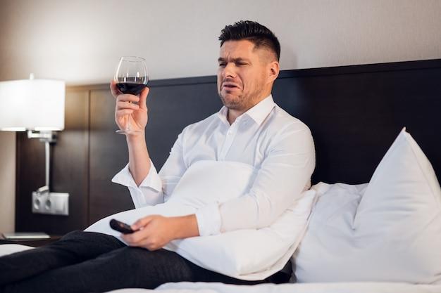 Geschäftsmann mit einem glas rotwein im bett, fernsehend, ein lustiges gesicht machend, als ob er etwas ekelhaftes im fernsehen sieht