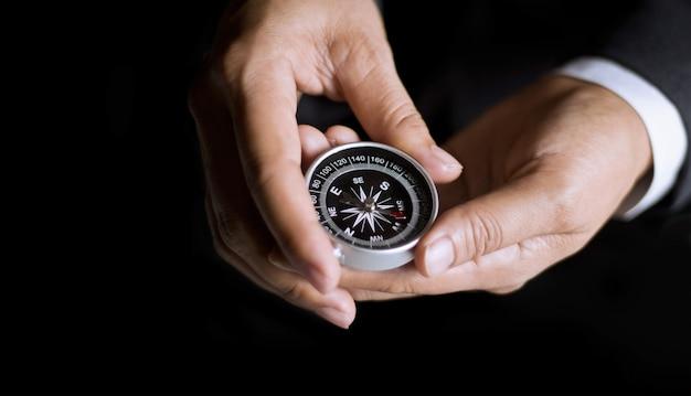 Geschäftsmann mit einem kompass, der in der hand auf dunklem hintergrund hält