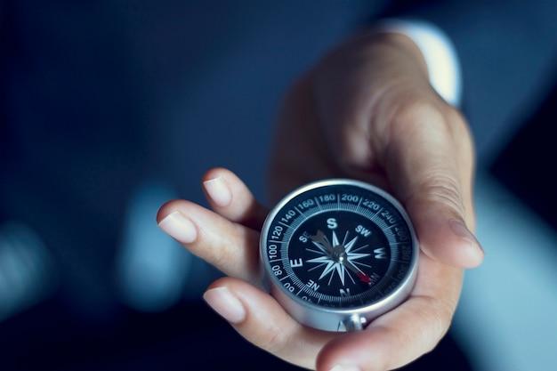 Geschäftsmann mit einem kompass, der in der hand, farbtonfilmblick hält Premium Fotos