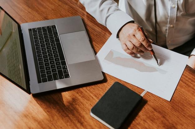 Geschäftsmann mit einem laptop, der auf ein papier schreibt
