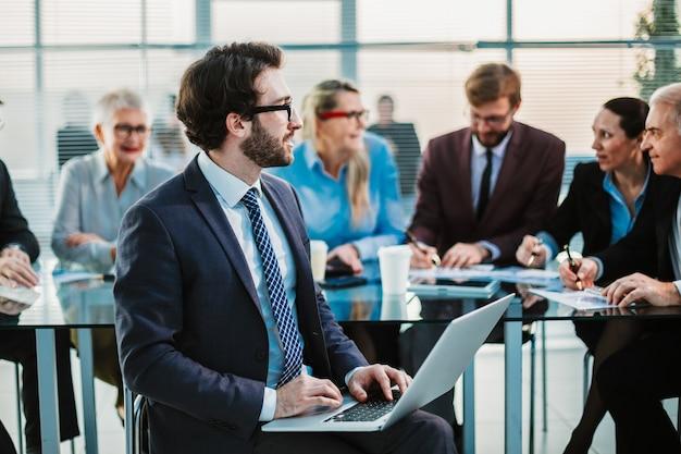 Geschäftsmann mit einem laptop, der vor einem büro-schreibtisch sitzt. menschen und technologie