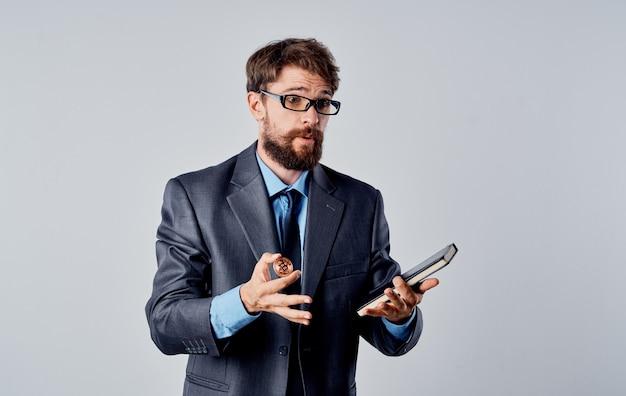 Geschäftsmann mit einem notizblock in seinen händen auf einem grauen hintergrund und einer bitcoin-kryptowährungsmünze. hochwertiges foto