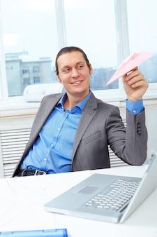 Geschäftsmann mit einem papierflugzeug spielen