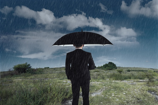 Geschäftsmann mit einem regenschirm, der unter dem regen steht