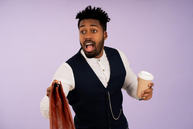 Geschäftsmann mit einem schockierten gesichtsausdruck, während er eine tasse kaffee und eine aktentasche vor isoliertem hintergrund hält. geschäftskonzept.