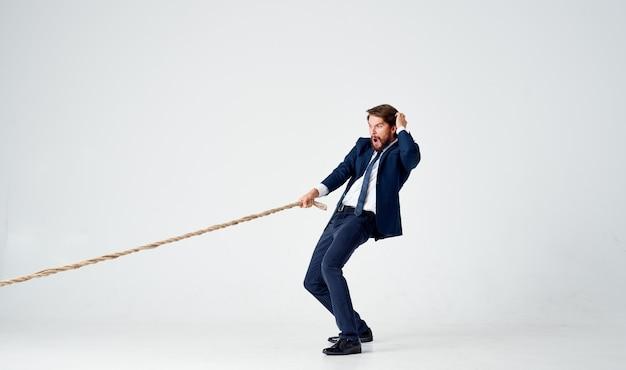 Geschäftsmann mit einem seil in seinen händen auf einem leichten hintergrundspannungsmodell des erreichens des ziels. hochwertiges foto