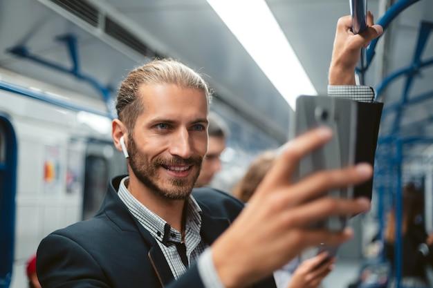 Geschäftsmann mit einem smartphone, das in einem u-bahnzug steht