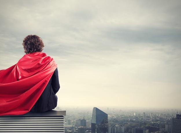 Geschäftsmann mit einem superheldenkapblick von oben über der stadt