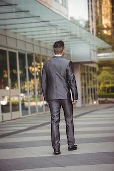 Geschäftsmann mit einem tagebuch, das im bürocampus geht