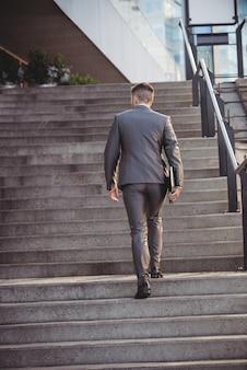 Geschäftsmann mit einem tagebuch steigt die treppe hinauf