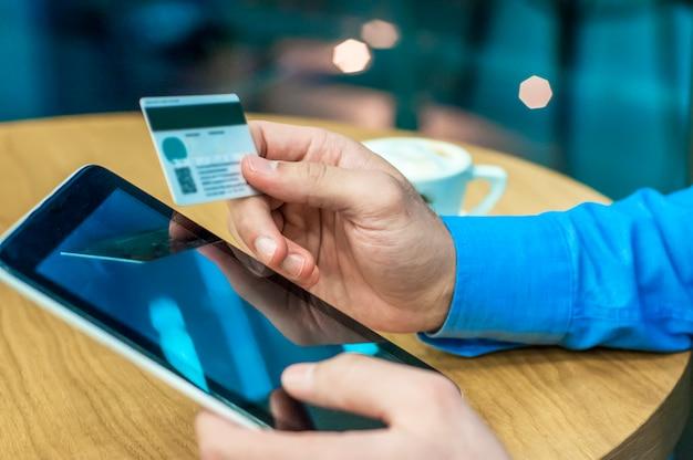 Geschäftsmann mit einer kreditkarte und digitale tablette für den kauf online. mann kauft im internet