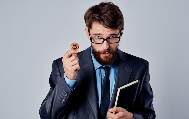 Geschäftsmann mit einer münze in seinen händen und einem grauen hintergrund des notizbuchgeschäfts. hochwertiges foto