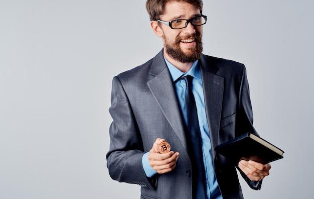 Geschäftsmann mit einer münze in seinen händen und in einer jacke auf einem grauen hintergrund, der mit seinen händen bitcoin-kryptowährung gestikuliert