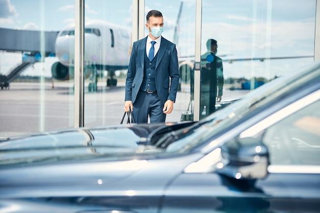 Geschäftsmann mit einer tasche in der hand, der nahe der glastür eines flughafens steht und das auto vor ihm betrachtet. medizinische maske auf seinem gesicht