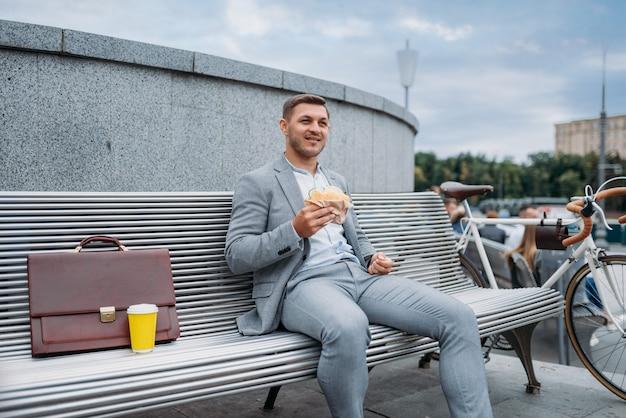 Geschäftsmann mit fahrrad isst auf der bank im bürogebäude in der innenstadt zu mittag.
