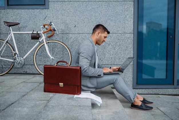 Geschäftsmann mit fahrrad und laptop beim mittagessen im bürogebäude in der innenstadt.