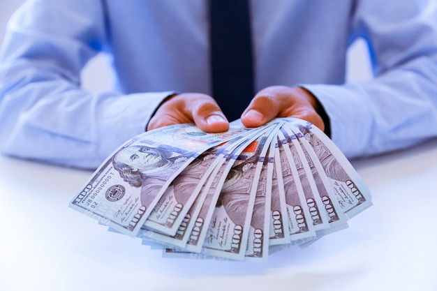 Geschäftsmann mit geld in der hand, us-dollar, investition, erfolg und rentablen geschäftskonzepten.