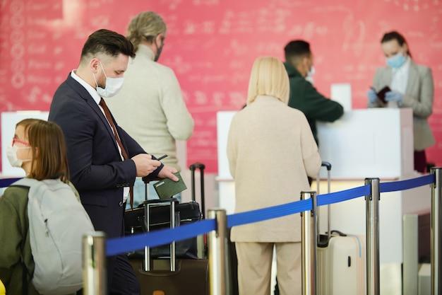 Geschäftsmann mit gepäck auf geschäftsreise, der eine nachricht auf dem handy eingibt, während er in einer warteschlange am flughafen steht