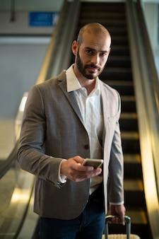 Geschäftsmann mit gepäck unter verwendung des mobiltelefons