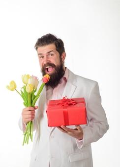 Geschäftsmann mit geschenk und strauß tulpen zum geburtstag romantischer mann bärtiger mann halten blumenstrauß von
