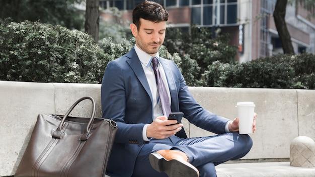 Geschäftsmann mit getränk unter verwendung des smartphone
