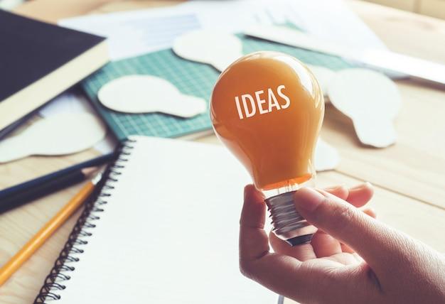 Geschäftsmann mit glühbirne auf schreibtisch am arbeitsplatz