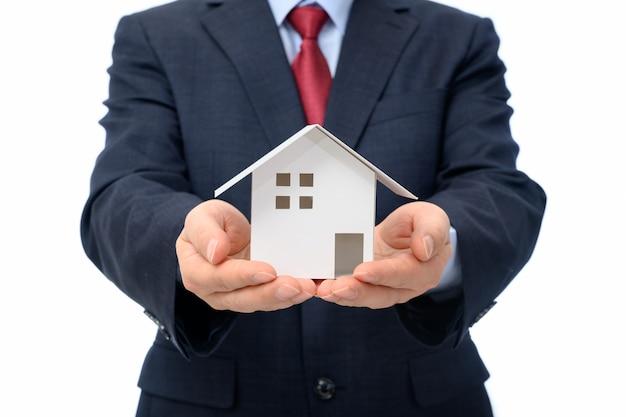 Geschäftsmann mit hausmodell an hand. immobilien-konzept.