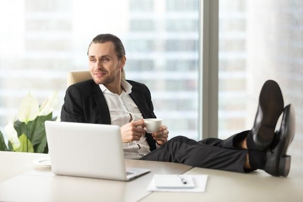 Geschäftsmann mit kaffee stellt sich glückliche zukunft vor