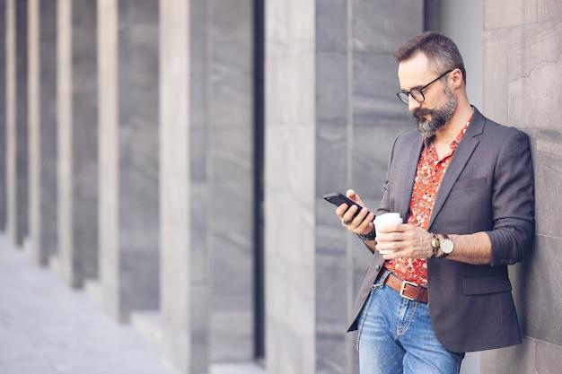 Geschäftsmann mit kaffee unter verwendung des mobiltelefons