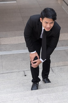 Geschäftsmann mit knieschmerzen, hinderniskonzept