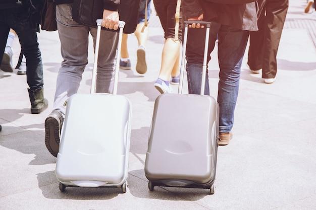 Geschäftsmann mit koffer auf straßenstraße reisender mit gepäck gehend hektik überschrift gehen zum flughafen. gepäckreise. weicher fokus.